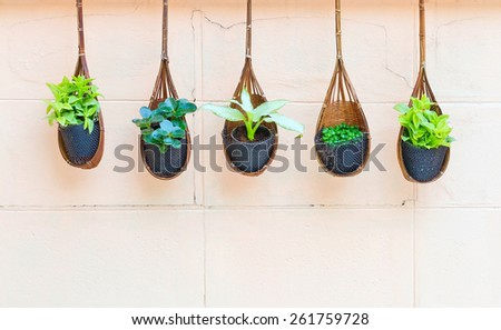 Flowers in the basket on a brick wall background. - stock photo
