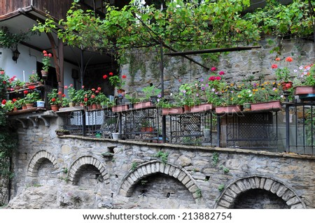 Flowers in the flowerpots and planters in the shadowy garden of the Old Town in Veliko Tarnovo in Bulgaria - stock photo