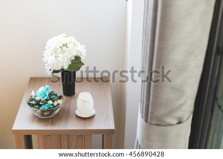 Flowers in vase next on wooden desk in Luxury Upscale Home - stock photo