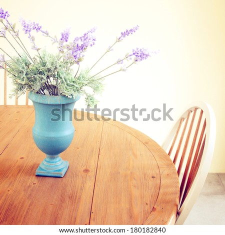Flowers in vase on the table with retro filter effect - stock photo