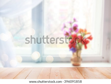 Flowers in vase on the window with wooden background