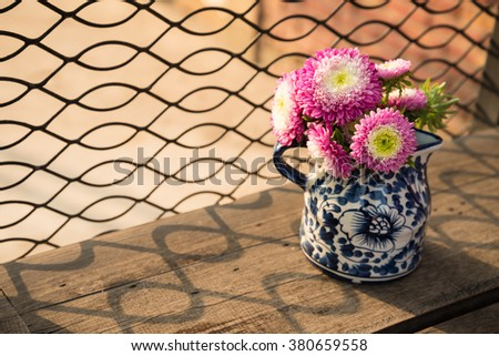 Flowers in vase with sunlight on wood table - stock photo