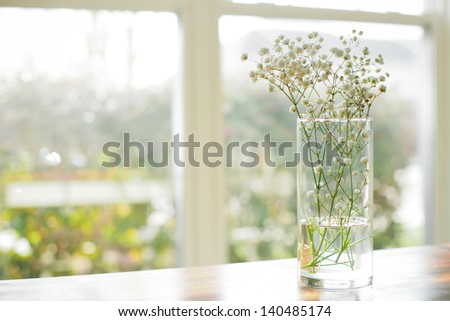 Flowers in watered vase sit on a wooden table in front of windows - stock photo