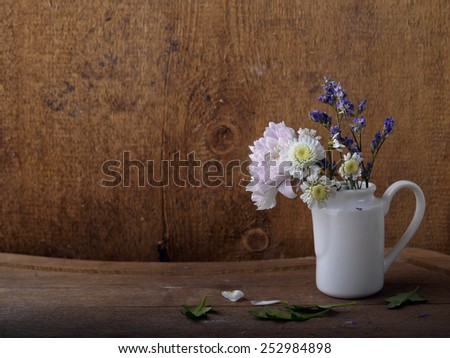 Flowers in watering-can, isolated on the wood background