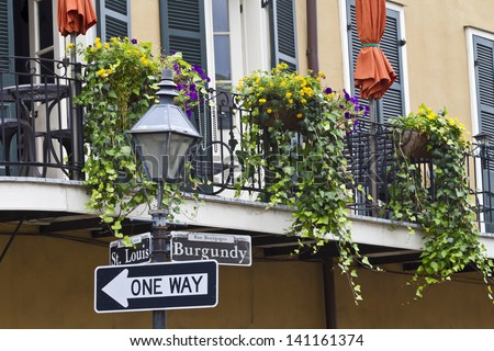 Flowers, ivy and Mardi Gras beads drape over a balcony railing on the corner of Burgundy & St. Louis in the French Quarter of New Orleans, Louisiana - stock photo