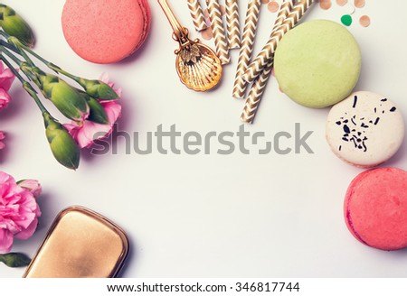 Flowers, macarons, paper straws in pastel color and golden box, top view, retro toned photo