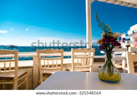 flowers on a table in little venice, mykonos, greece. - stock photo
