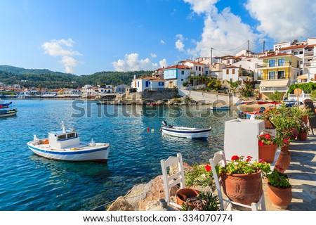 Flowers on shore with fishing boats in Kokkari port, Samos island, Greece - stock photo