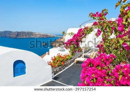 Flowers on the terrace. Beautiful landscape with sea view. White architecture on Santorini island, Greece. - stock photo