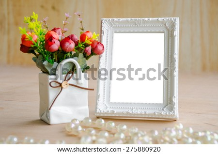 Flowers vase and blank white picture frame on wooden background, clipping path. - stock photo