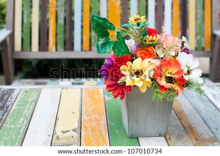 Flowers vase put on the old paint wood table - stock photo