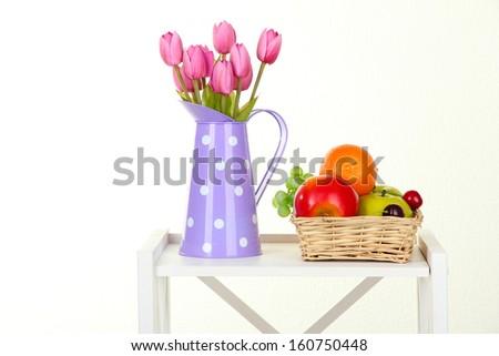 Flowers with fruit on white shelf on grey wall background - stock photo