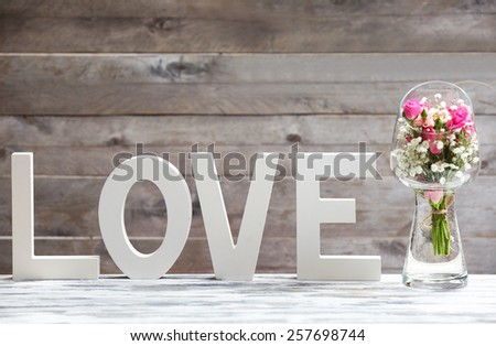 Flowers with word Love on wooden planks background - stock photo