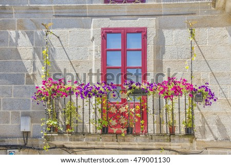 Flowery balcony with red door in the old town of Lugo