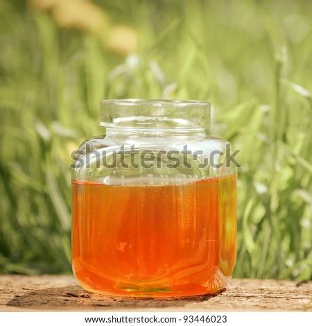 Flowery honey in glass jar on wooden table against spring natural background - stock photo