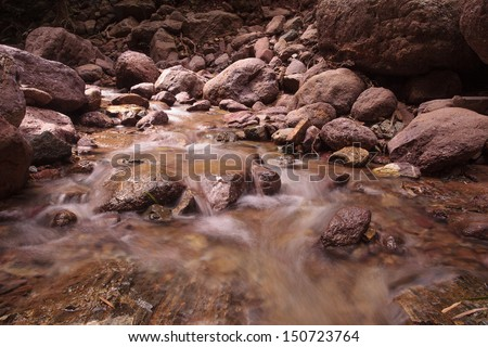 flowing river in forest - stock photo