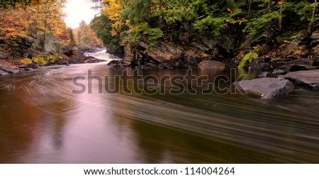 Flowing river with fall colors in the distance. - stock photo