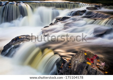 Flowing whitewater cascades over rock ledges at Bond Falls, a waterfall in Michigan's Upper Peninsula. - stock photo