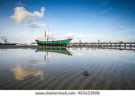 flreflection of fishing boat on tropical beach - stock photo