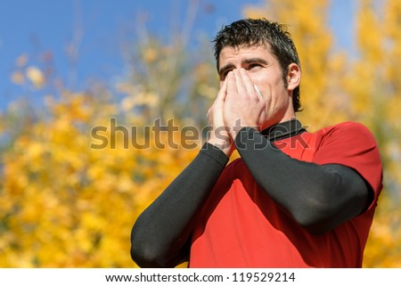 Flu and cold man. Young athlete coughing and blowing on a tissue. Caucasian hispanic male model. - stock photo