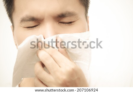 Flu cold & allergy symptom. Closeup of sick asian man with fever sneezing in tissue,  Sepia film processed - stock photo