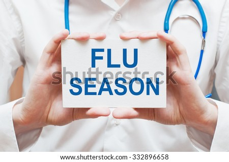 Flu Season card in hands of Medical Doctor - stock photo