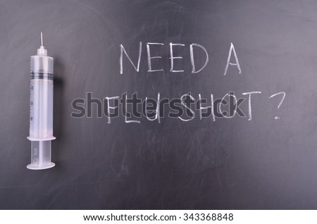 Flu Vaccine Concept with syringe and blackboard message - stock photo