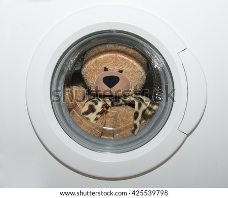 Fluffy bear toy in washing machine - stock photo