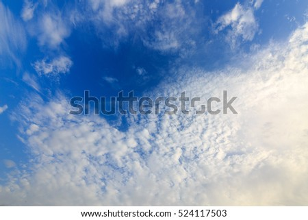 Fluffy clouds at dark blue sky
