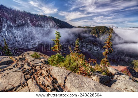 Fluffy fog emerging from rocky formation in the mountains - stock photo