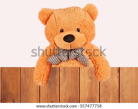 fluffy plush teddy bear over wooden fence, studio shot - stock photo