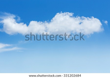 fluffy single cloud on clear blue sky background - stock photo