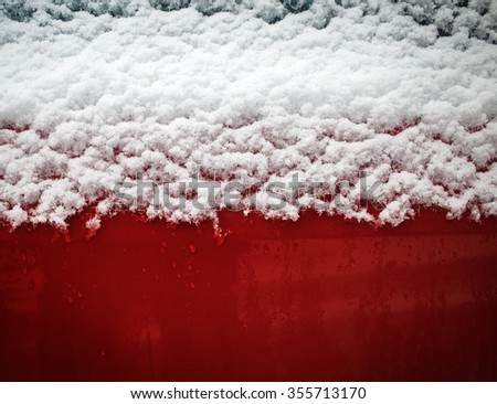 Fluffy snow flakes on the red metal background. - stock photo