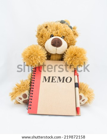 "Fluffy teddy bear holding a notebook with the words ""MEMO"" - stock photo"