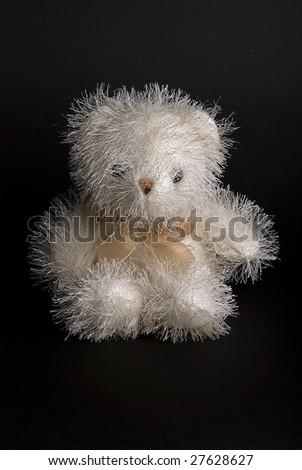 Fluffy teddy bear toy on black background - stock photo