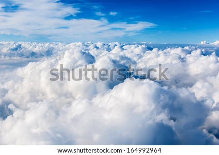 Fluffy white clouds and blue sky seen from airplane. - stock photo