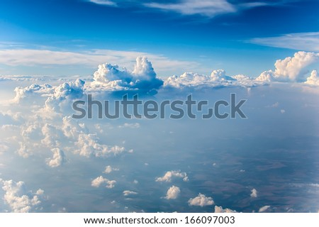 Fluffy white clouds and blue sky seen from airplane