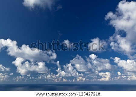 Fluffy white clouds over a deep blue sky and sea. - stock photo