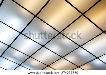 Fluorescent lamps on the modern ceiling. Luminous ceiling of square tiles. - stock photo