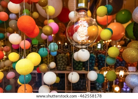 Fluorescent light bulb and ball decorations in a window.