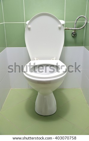 Flush toilet with white and green tiles in background, front view - stock photo