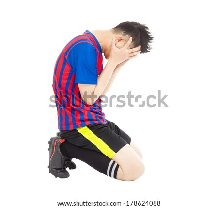 flushed football player kneeling down - stock photo