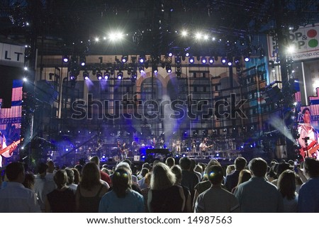 FLUSHING, NY - JULY 16: Concert goers watch singer Billy Joel on stage as he performs at Shea Stadium on July 16, 2008 in Flushing, New York. - stock photo