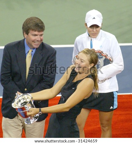 FLUSHING, NY - SEPT 9: Maria Sharapova (RUS) (C) holds her trophy after beating Justine Henin-Hardenne (BEL) to win the ladies singles final at the U.S. Open on September 9, 2006 in Flushing, New York - stock photo