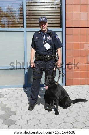 FLUSHING, NY- SEPTEMBER 8: NYPD transit bureau K-9 police officer and German Shepherd  K-9 Taylor providing security at National Tennis Center during US Open 2013 on September 8, 2013 in Flushing . - stock photo