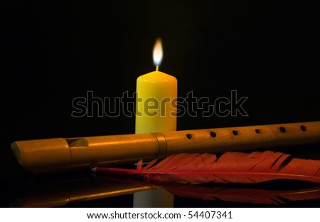 Flute, burning candle and red feather