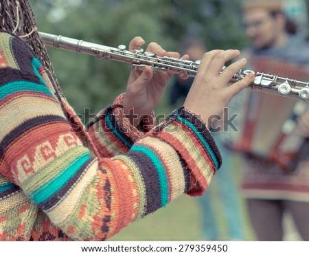Flute in the girl's hands in the foreground with bokeh effect. Funny street musicians playing in the park on the flute and the accordion. - stock photo