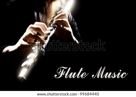Flute music. Musical instrument with flutist hands isolated on black. Details of playing, focus is on the right hand. - stock photo