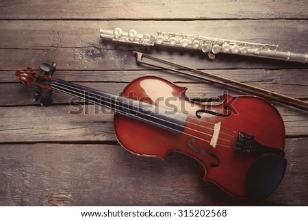 Flute with violin on table close up