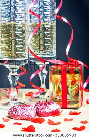 Flutes of champagne in holiday setting. Romantic evening , candles and gift. Postcard on Valentine's Day